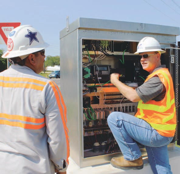 David Smith, at right, TxDOT Traffic Signal Specialist, preparing to turn on traffic signal lights at SH 97 and Airport Road. At left is Rolando Morales, Electrical Foreman with EV Bel Contractors. See story on Page 8.