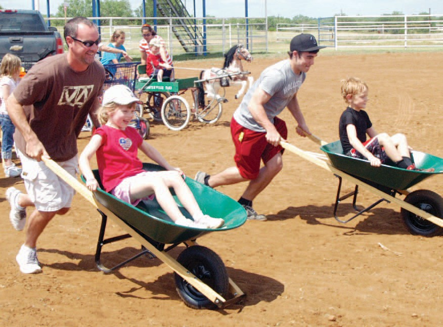 Fun was had by all this past weekend at the first annual Redneck Games to support CASA. Pictured left to right is Chris Griffin pushing Madison Carr and Dillon LIght pushing Tanner Desjardin in a wheelbarrow race. The race was one of many fun events during the weekend. The weekend event raised over $5,000 to help Court Appointed Special Advocates.