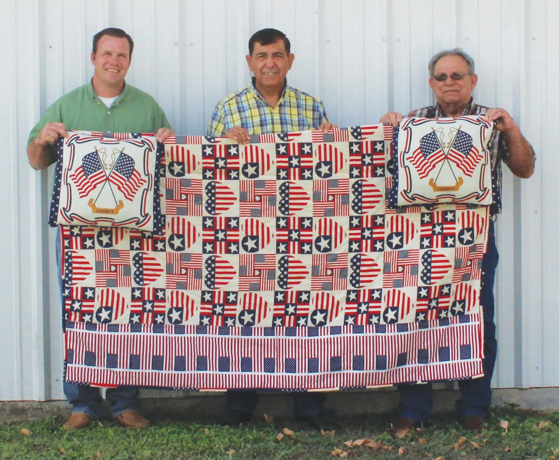 St. Ignatius Catholic Church in Christine is preparing for their annual picnic to be held this Sunday, September 2. Inviting you to the big auction are the Committee Council members Greg Vyvlecka, Robert Regalado and Aurelio Bosquez. One of the featured auction items is this beautiful quilt, handmade and donated by Dominga Bautista. MIssing from photo is committee member Pete Martinez.