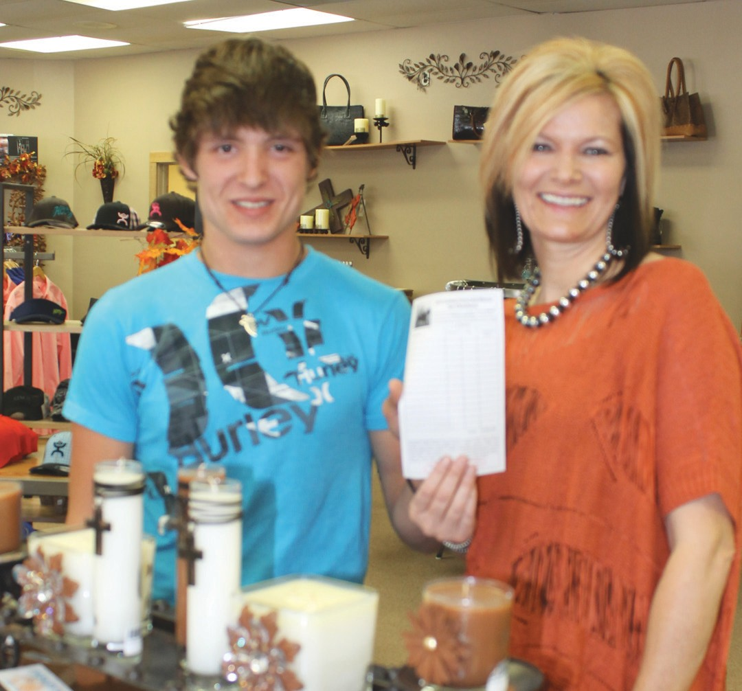 Sheila Crouch, owner of Paisley's Boutique, congratulates Ian Chachere on his winning entry for Cowboy Crazy Cash. Ian won a $500 shopping spree after he registered at Paisley's.