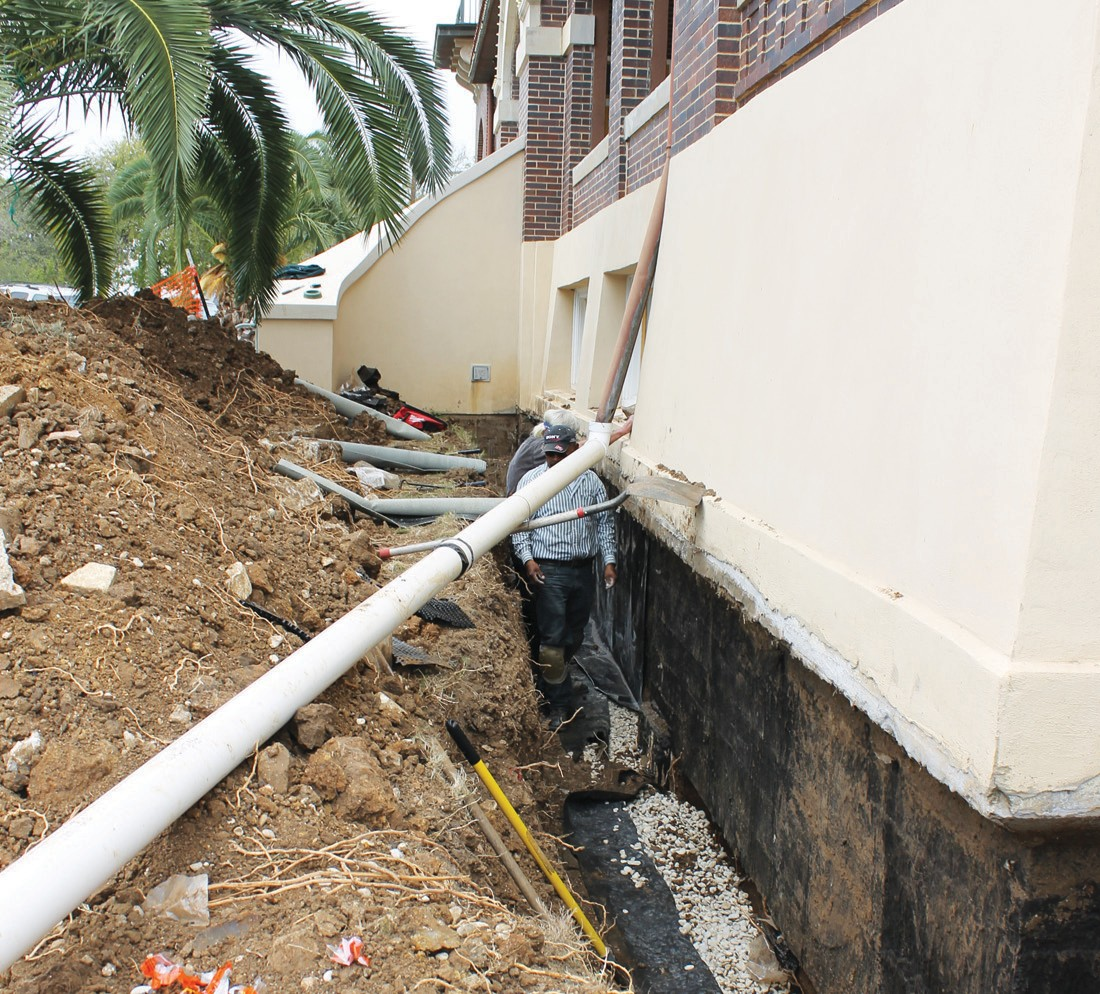 Work being done alongside the west side of Atascosa County Courthouse where a moisture barrier will be inserted.