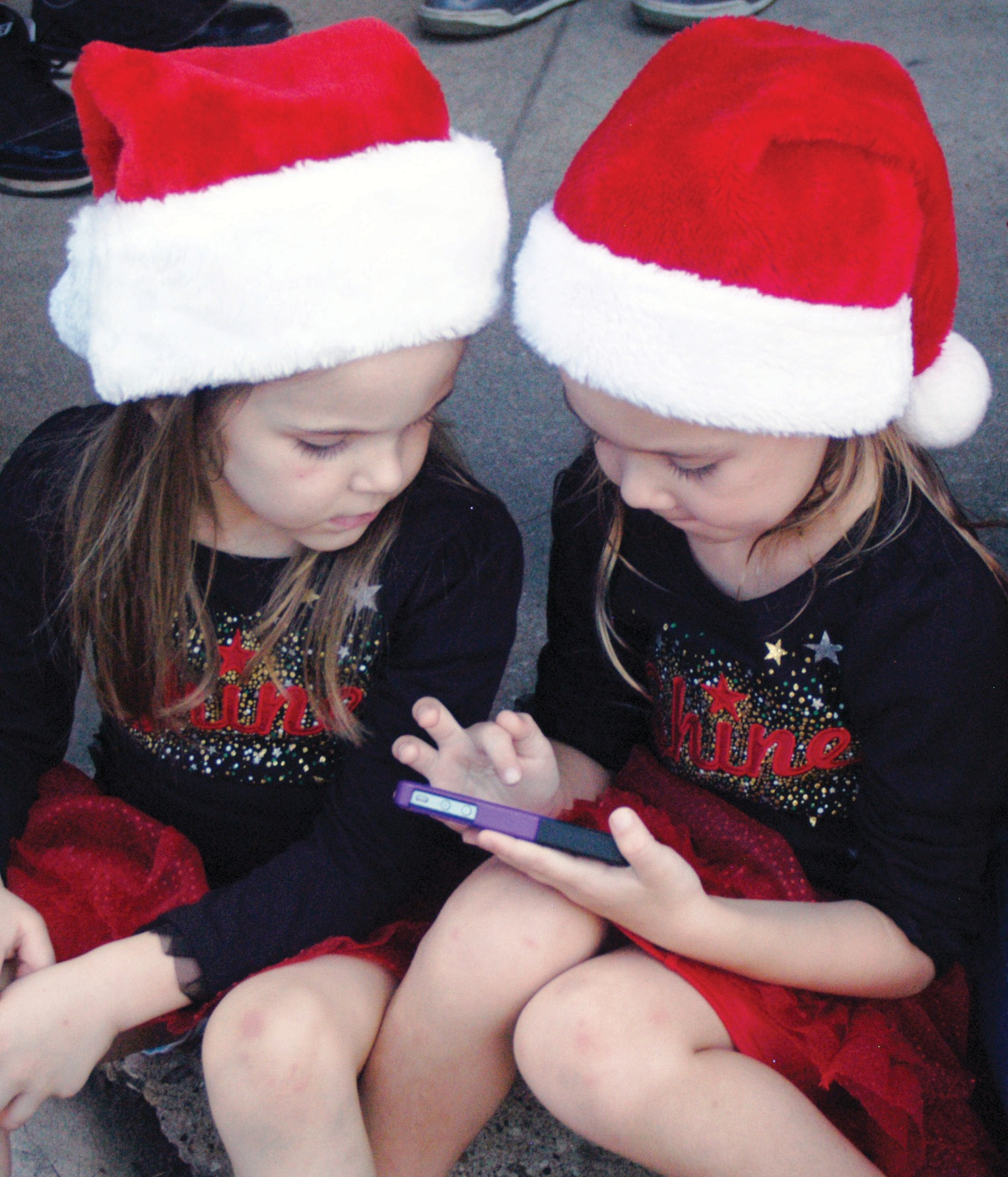 Kid Nation Dancers Kiera Wiatrek and Savanna Schuchart look as though they may be texting Santa with their wish list at the Brush Country Christmas event held last Saturday. The girls also performed with other dancemates in downtown Pleasanton.