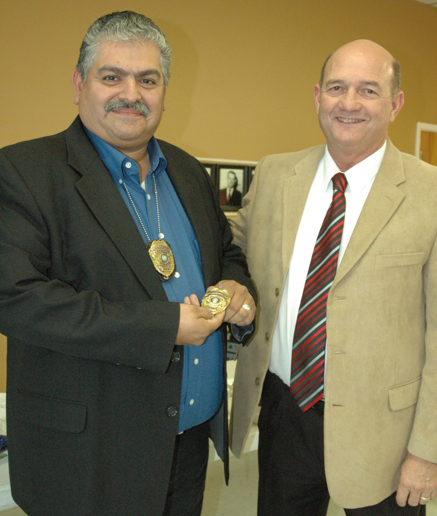 Pleasanton City Manager Bruce Pearson (right) presents the Chief of Police badge to Ronald Sanchez during the annual Christmas luncheon held December 5.