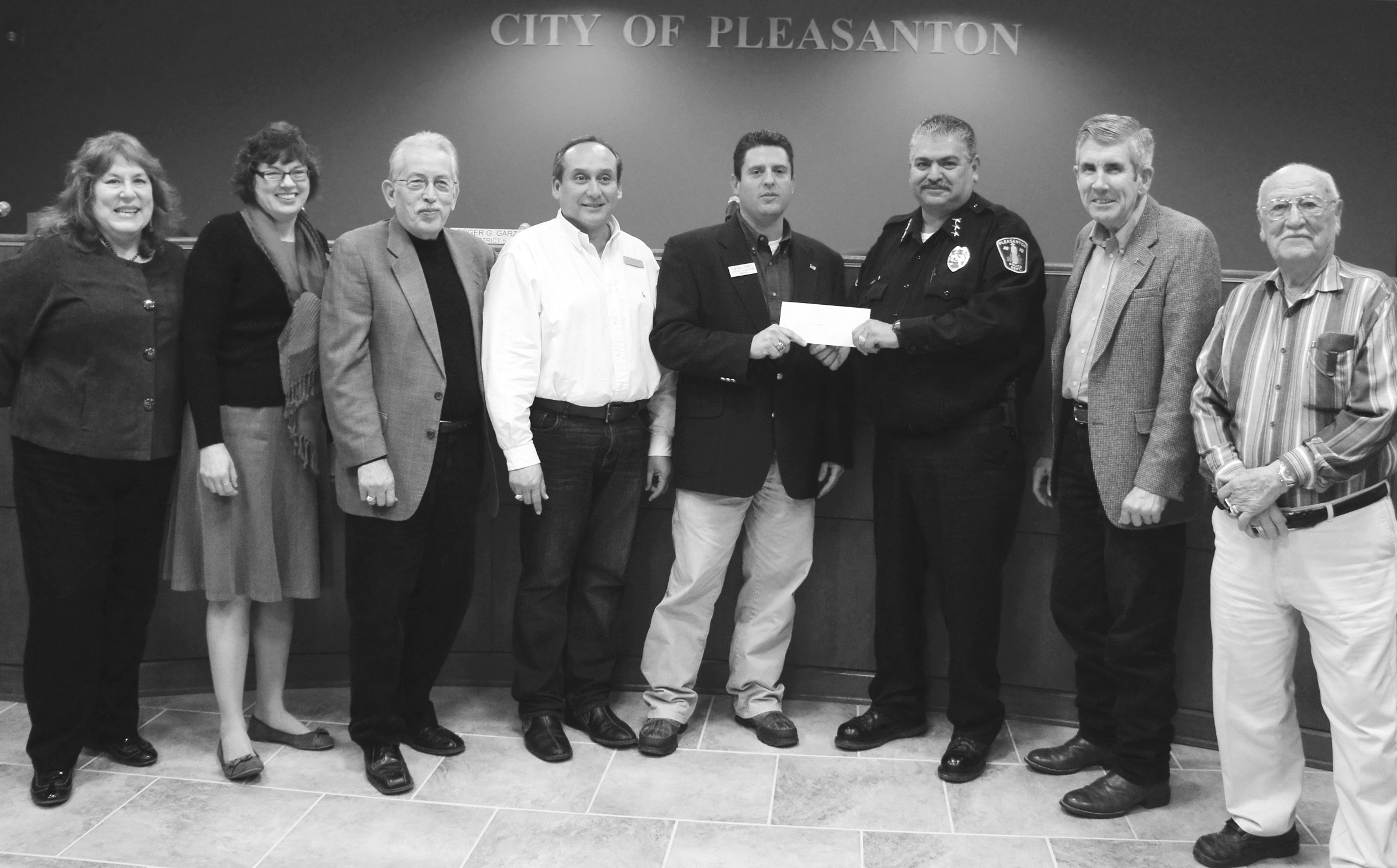 The City of Pleasanton received an $8,000 donation to continue the K-9 program. Left to right are: Jeanne B. Israel, Kathy Coronado, Roger G. Garza, J.R. Gallegos, Mayor Clinton J. Powell, Police Chief Ronald Sanchez, Jimmy Magel and Abraham Saenz.