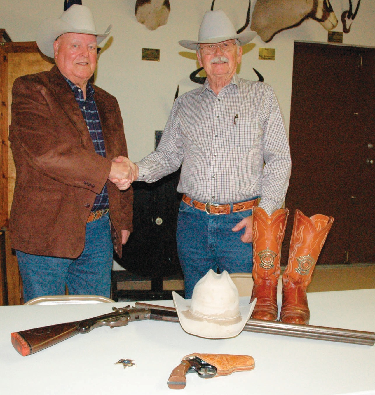 Former Atascosa Sheriff Tommy Williams officially turns over his memorabilia to Longhorn Museum Society President J. D. Kvapil. Included in the donation from Atascosa County's longest seated Sheriff to the museum are his original Stetson cowboy hat, custom boots, personalized badge, a pistol and a triple-barreled shotgun.