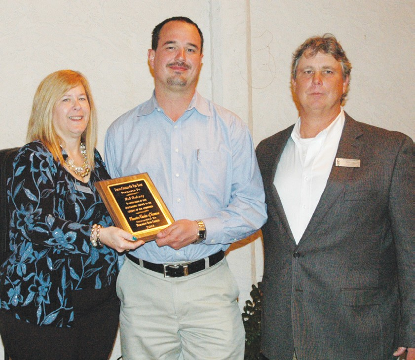 Walt Rakowitz, center, receives his plaque for Young Citizen of the Year from Chamber director Sharon LaGrange and Pleasanton Young Farmers' representative Chico Cox.