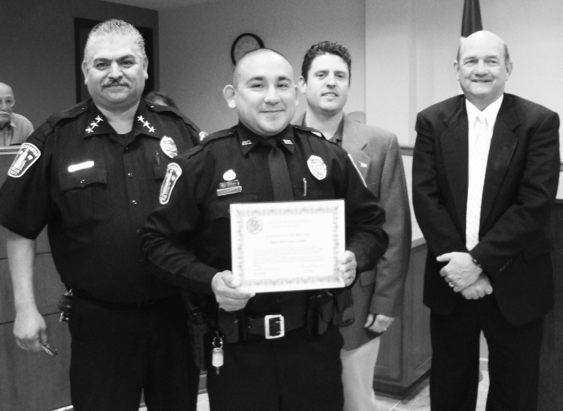 Pleasanton Police Chief Ronald Sanchez awards a certificate of bravery to Officer Jason Velasquez for his efforts to ensure a burning home was empty. Mayor Clint Powell and City Manager Bruce Pearson offer their gratitude.