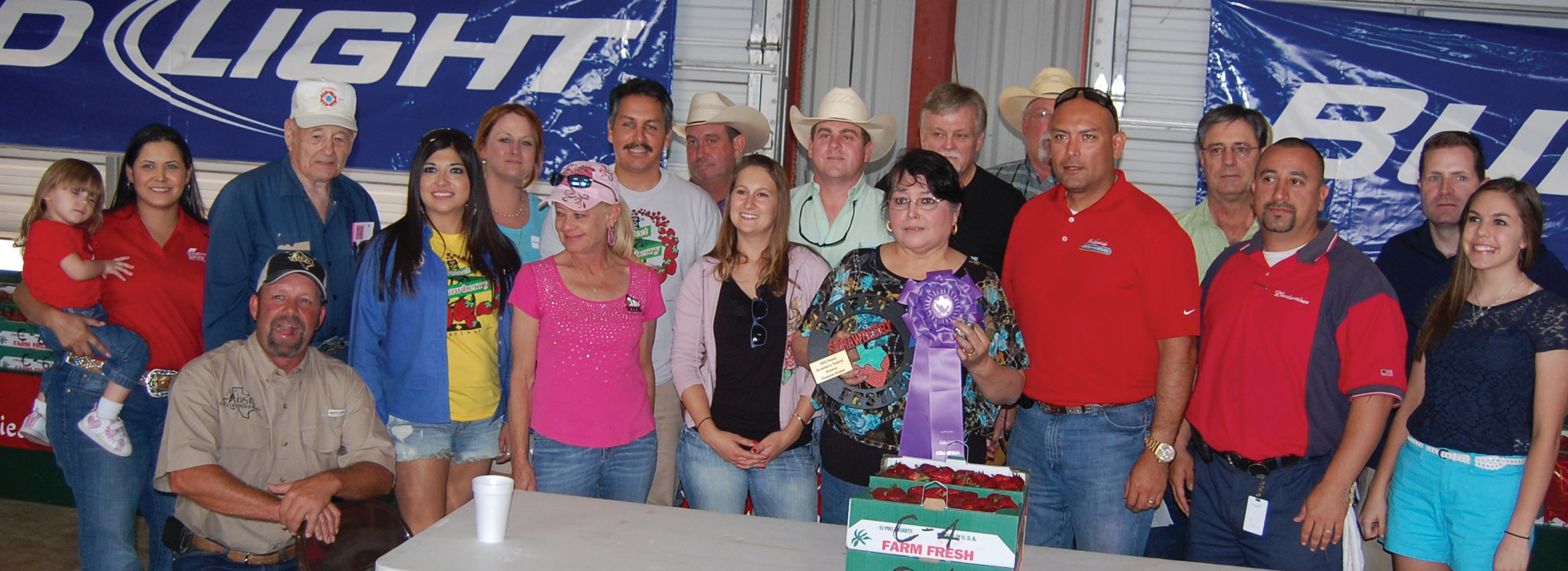 Stella Reyes was the Grand Champion winner at this year's Poteet Strawberry Festival Auction. Her prize-winning berries sold for $13,100. She is joined by bidders, left to right: Ginnie Otto holding Mariana (Security Service Federal Credit Union), Jerome Korus (Poteet VFW), Jimmy Howe (DSD Environmental), Jackie Brown (Security State Bank), Ginger Walker (Poteet Country Winery), Dawn Mason (South Texas Que & Brew), Louis Ramos (Poteet Rotary Club and Ramos Tire & Automotive Service, Mark Biediger (Pure Party Ice), Natalie Wolff and Casey Bartek (Bartek Construction), winning grower Stella Reyes, Bob Hurley (Hurley Auto Parts, Plestex Theatre and Hurley Funeral Home), Robert Mason (South Texas Que & Brew), Ben Garcia (Bud Light-Silver Eagle Distributors), Eldon Tuttle (Tuttle Motor Co.), Jason Olvera (Bud Light-Silver Eagle Distributors), Cory Oliver (H-E-B) and Katie Harkrider (H-E-B).