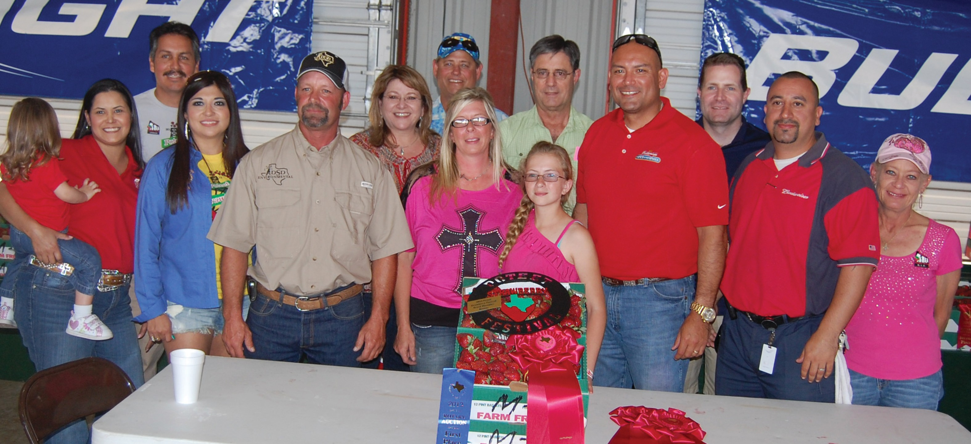 Jessica Cochrane grew this year's Reserve Grand Champion berries at the auction on Saturday. She is joined by the bidders, left to right: Ginnie Otto holding Mariana (Security Service Federal Credit Union, Louis Ramos (Poteet Rotary Club and Ramos Tire & Automotive Service), Jackie Brown (Security State Bank), Jimmy Howe (DSD Environmental), Nellie Delgado (AEP Texas), Pat Paxson (Pure Party Ice), winning grower Jessica Cochrane with daughter Toccoa Cochrane, Eldon Tuttle (Tuttle Motor Co.), Ben Garcia (Bud Light-Silver Eagle Distribution), Cory Oliver (H-E-B), Jason Olvera (Bud Light-Silver Eagle Distributors) and Dawn Mason (South Texas Que & Brew).