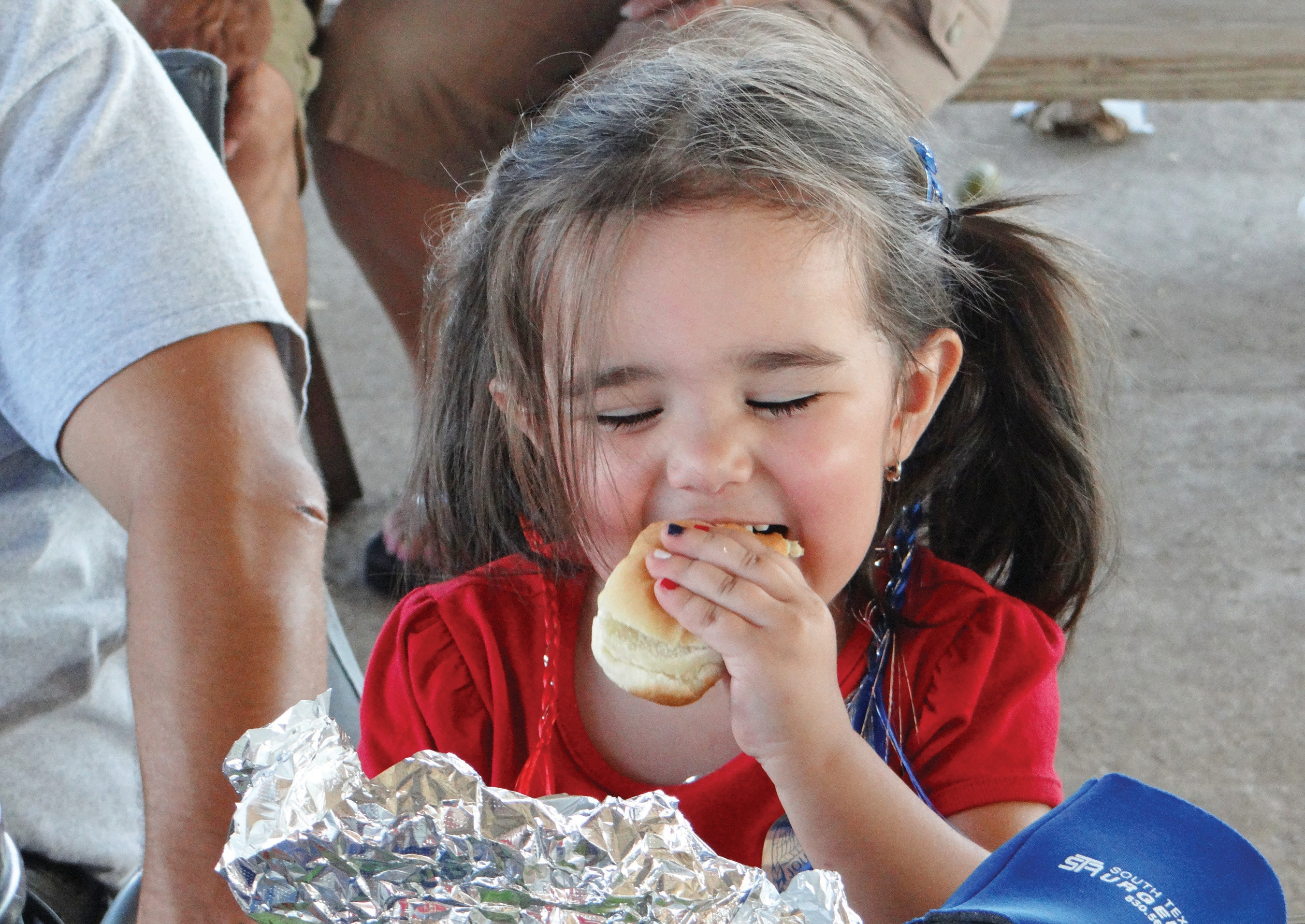 Alexus Longoria of Pleasanton bites into a hot dog during the American Pride Day celebrating July 4th at the Jourdanton City Park.