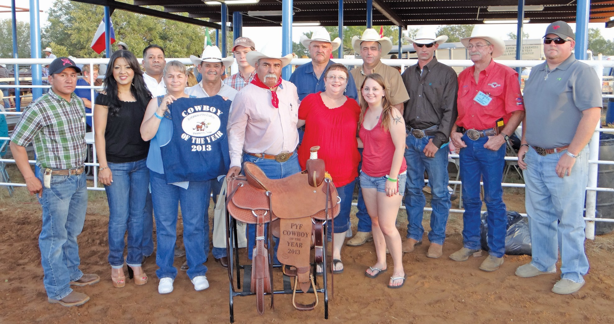 The 2013 Atascosa County Working Cowboy of the Year was awarded to Roy Alonzo (center with saddle) at the Pleasanton Young Farmers Cowboy of the Year Rodeo and Festival held this past Friday, August 16. He was presented with a hand tooled Ringlestein saddle by the PYF members and Gus Wheeler of Atascosa Livestock Exchange who once again donated the saddle. He also received a plaque and bandanna from the committee and the traditional vest from the Pleasanton Chamber of Commerce. Left to right are Chamber Directors Jorge Quiroga, Claudia Reyes, Jason Reyes, Kellie Vrana, Cowboy Selection chair Joel McDaniel, Wheeler, Alonzo, Jo Ann Alonzo and their daughter Courtney and PYF members Darryl Ashley, Randy Rice, Dustin Neal, Roger Rowinsky and chamber director Wade McBee.