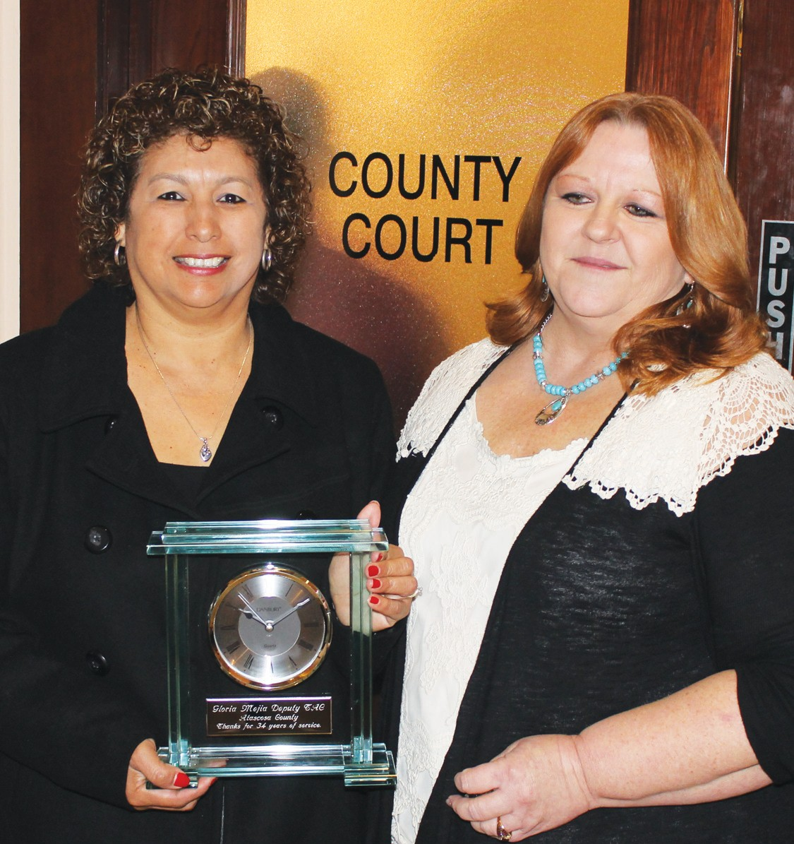 Gloria Mejia, left, receiving retirement plaque from Atascosa County Tax Assessor-Collector Loretta Holley. Gloria had seved as a Deputy Tax Assessor-Collector for a total of 34 years. She served in that position from November 7, 1977 to September 30, 1989 (12 years) and later from February 25, 1991 to December 31, 2013.