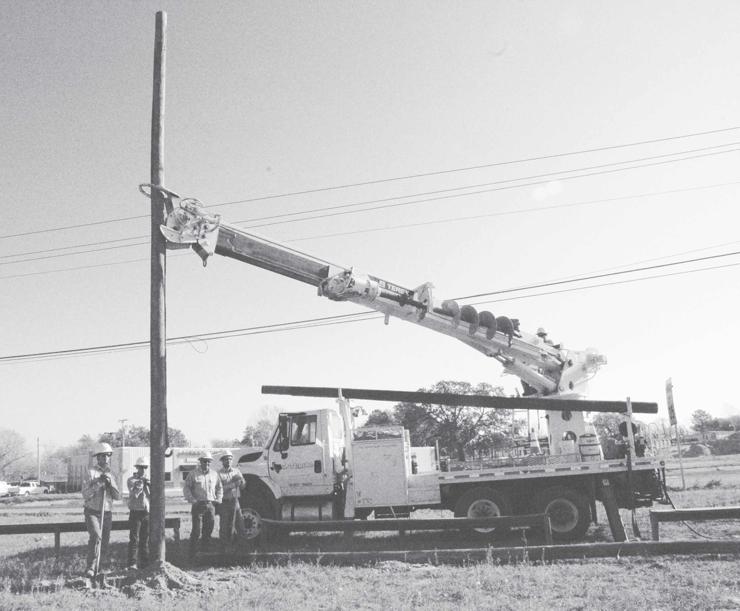 This Karnes Electric Cooperative crew set two poles near the Pleasanton Primary campus so a sign promoting safety around children could be displayed. Left to right are Josh Jaskinia, Allen Cardaway, Joe Escandon, Russell Korzeckwa and Teran Jurgatis is on the arm. The poles and efforts were donated by Karnes Electric.