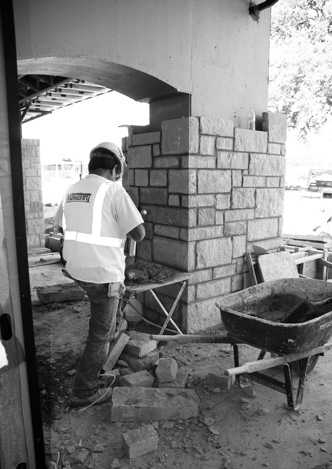 Mason sets the rock on the pillars on the east side of the buildings.