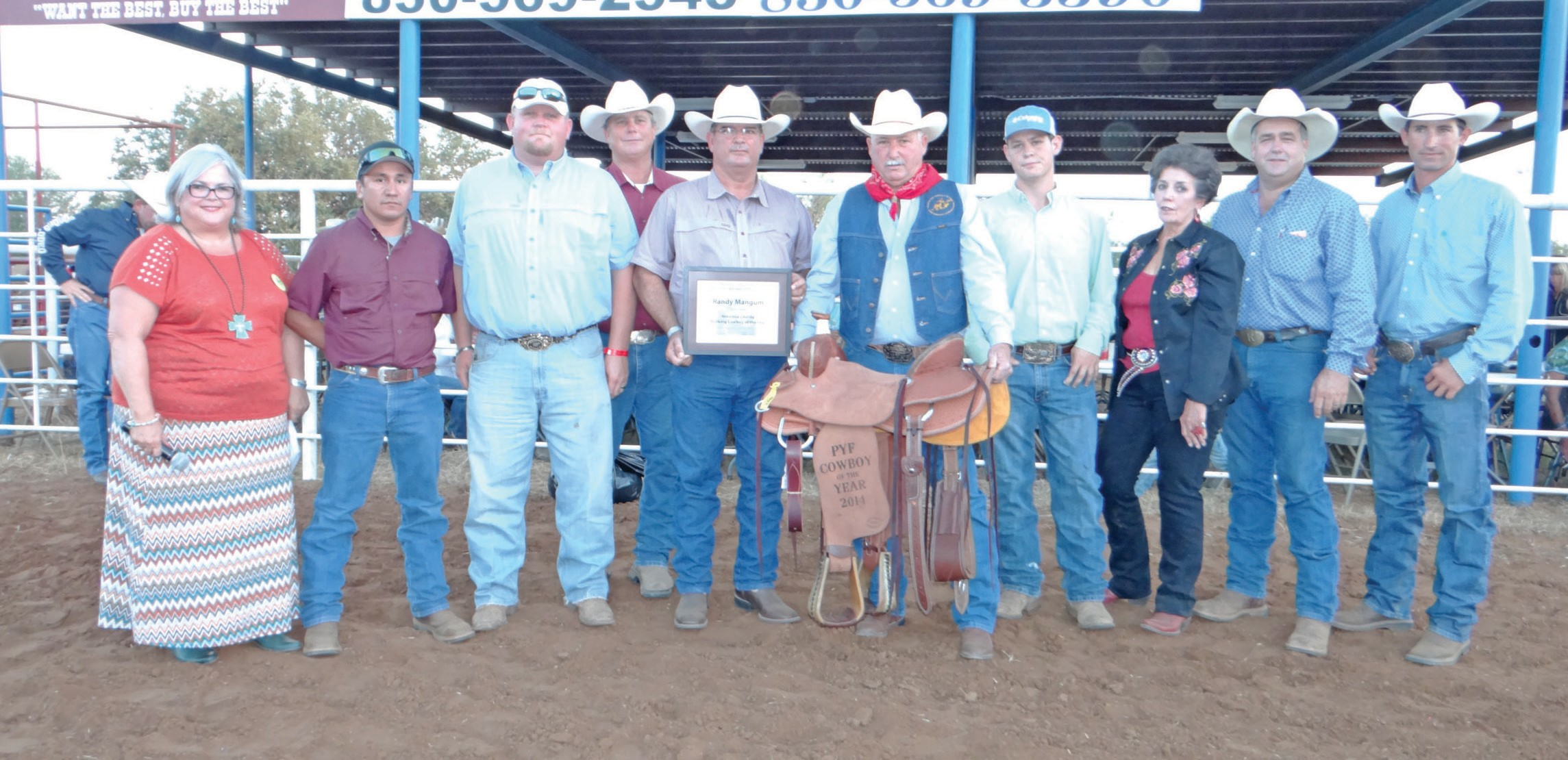 Randy Mangum (behind saddle) was named the 2014 Atascosa County Working Cowboy of the Year before the Pleasanton Young Farmers' rodeo on Friday, August 15. Mangum was given the saddle by the Young Farmers and it was donated by Atascosa Livestock Exchange. He also received a denim vest from the Pleasanton Chamber of Commerce, a bandana from Texas Moore, a bandana handmade rawhide slide from Roy Alonzo (2013 Cowboy of the Year) and a framed certificate from David McDaniel, 1997 Cowboy of the Year and donated by the Pleasanton Express. Left to right are Sue Brown, editor of the Pleasanton Express and emcee, Jorge Quiroga, Wade McBee and Chico Cox, Pleasanton Chamber of Commerce directors; David McDaniel, Randy Mangum, Gus Wheeler (Atascosa Livestock Exchange), Texas Moore, Randy Rice (Young Farmer) and Dustin Neal, Pleasanton Young Farmers president.
