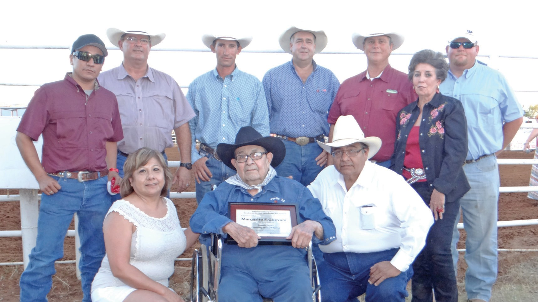 Margarito F. Guevara, seated, receives his certificate during his induction into the South Texas Cowboy Hall of Fame before the Pleasanton Young Farmers' Cowboy of the Year Open Rodeo on August 15. He is flanked by his daughter Margie Guevara-Clark and son Miguel Guevara. Helping with the presentation are, left to right, Jorge Quiroga, Pleasanton Chamber, David McDaniel (Cowboy of the Year 1997) Dustin Neal, President Pleasanton Young Farmers; Randy Rice, Pleasanton Young Farmers; Chico Cox, Texas Moore and Wade McBee, Pleasanton Chamber.