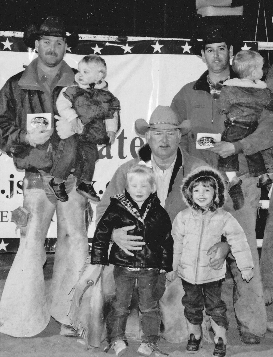 Randy Mangum, (kneeling with granddaughters Blye and Camry) and sons Clayton (with Rance) and Colby (with Layten) are proud winners at a ranch rodeo in Laredo.