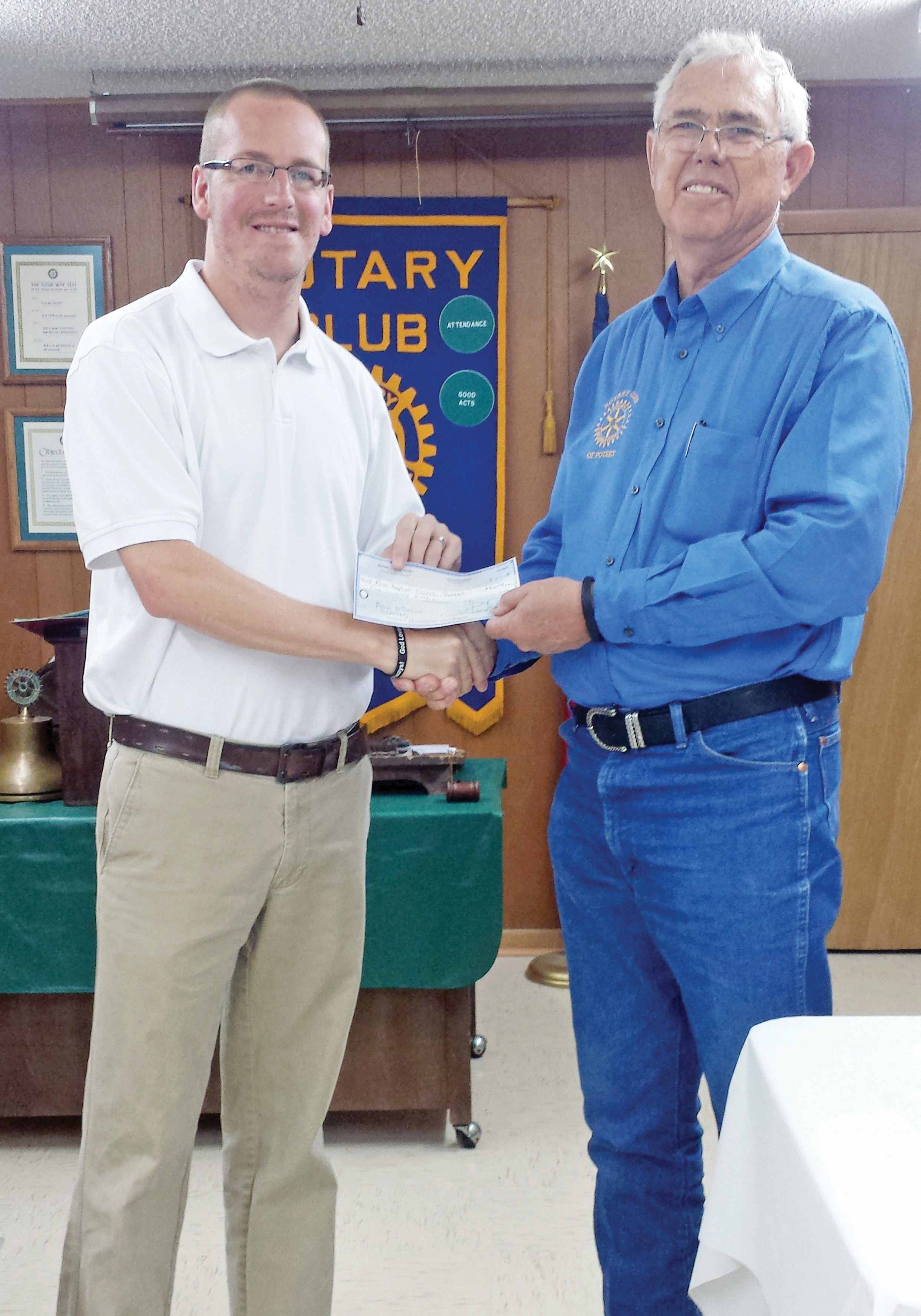 Mark Flack, new Pastor of First Baptist Church Poteet, accepts a check for $500 from Will Bates, on behalf of the Poteet Rotary Club. This donation will be used to provide school supplies for stuff the bus, which is then given to the teachers to disperse to those in need at Poteet ISD.