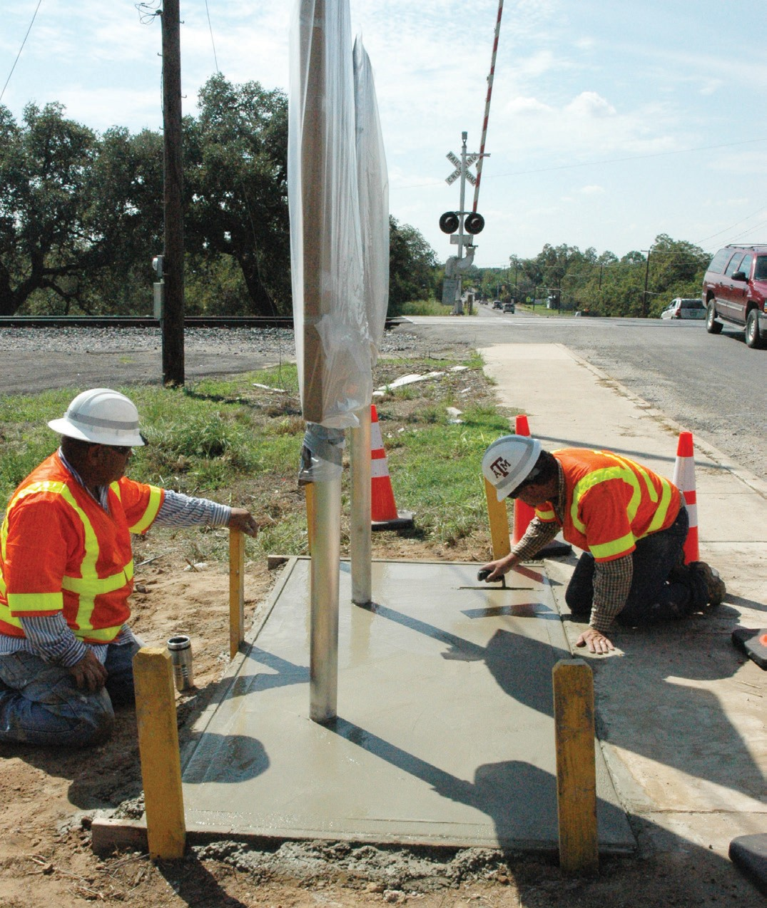 TxDOT employees, Johnny Hernandez (left) and Brian Jasik (right) put the finishing touches on the cement slab where two new markers - SAU&G Railroad and North Pleasanton - will be unveiled at the Atascosa Historical Commission's ceremony at 10 a.m. Saturday.
