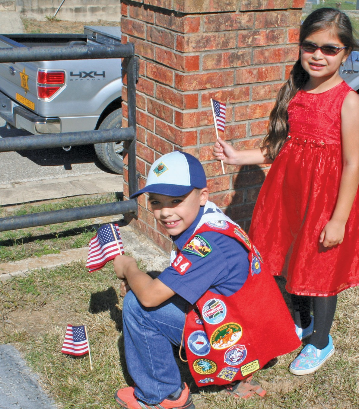 Cub Scout Zander Temple and Me-Too Angelina Ortiz place flags on fallen veterans graves.