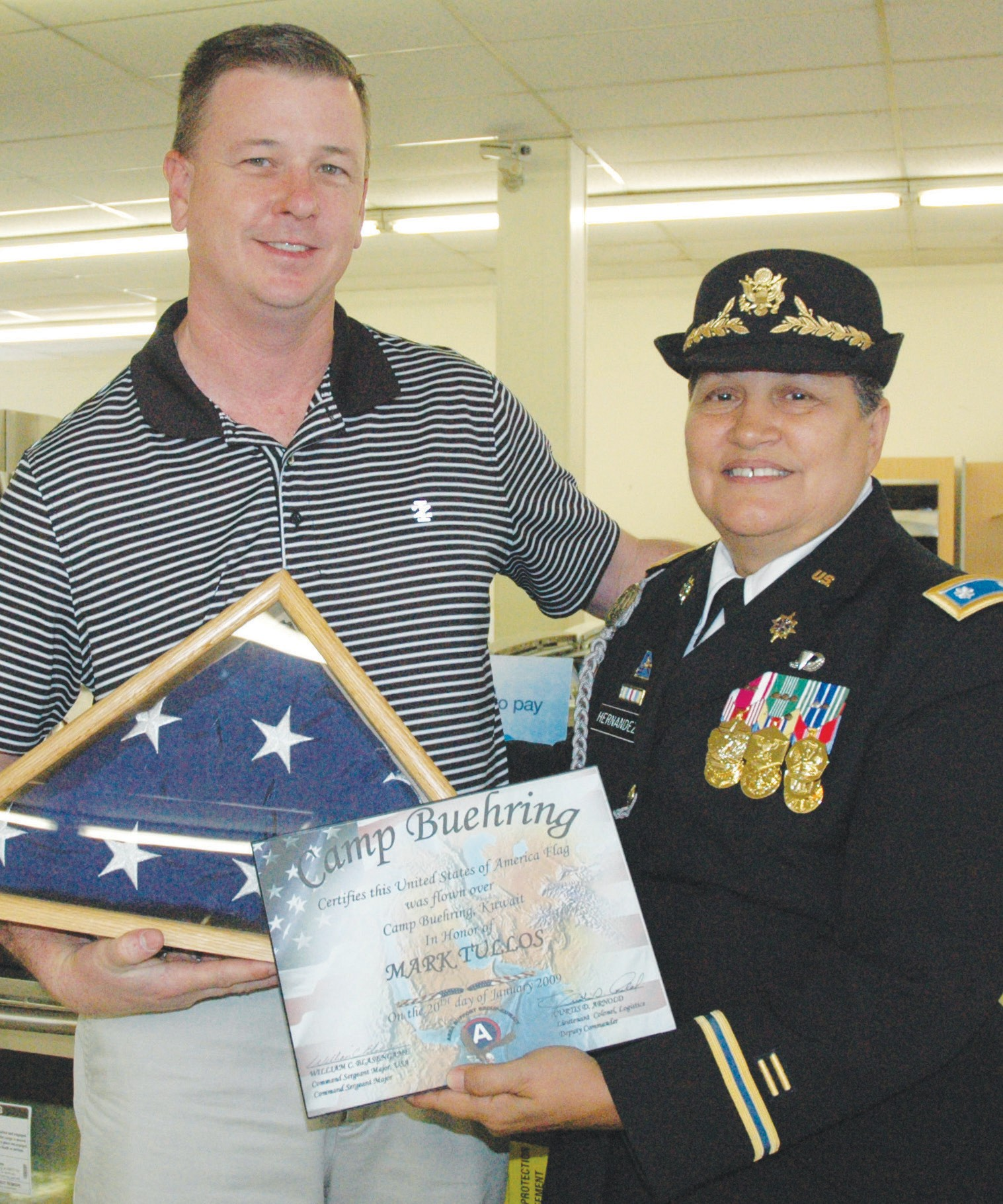 Mark Tullos, owner of the Sears store in Pleasanton, receives his flag, flown over Camp Buehring, Kuwait during LTC Retired U. S. Army Veronica R. Hernandez' tour in 2009.