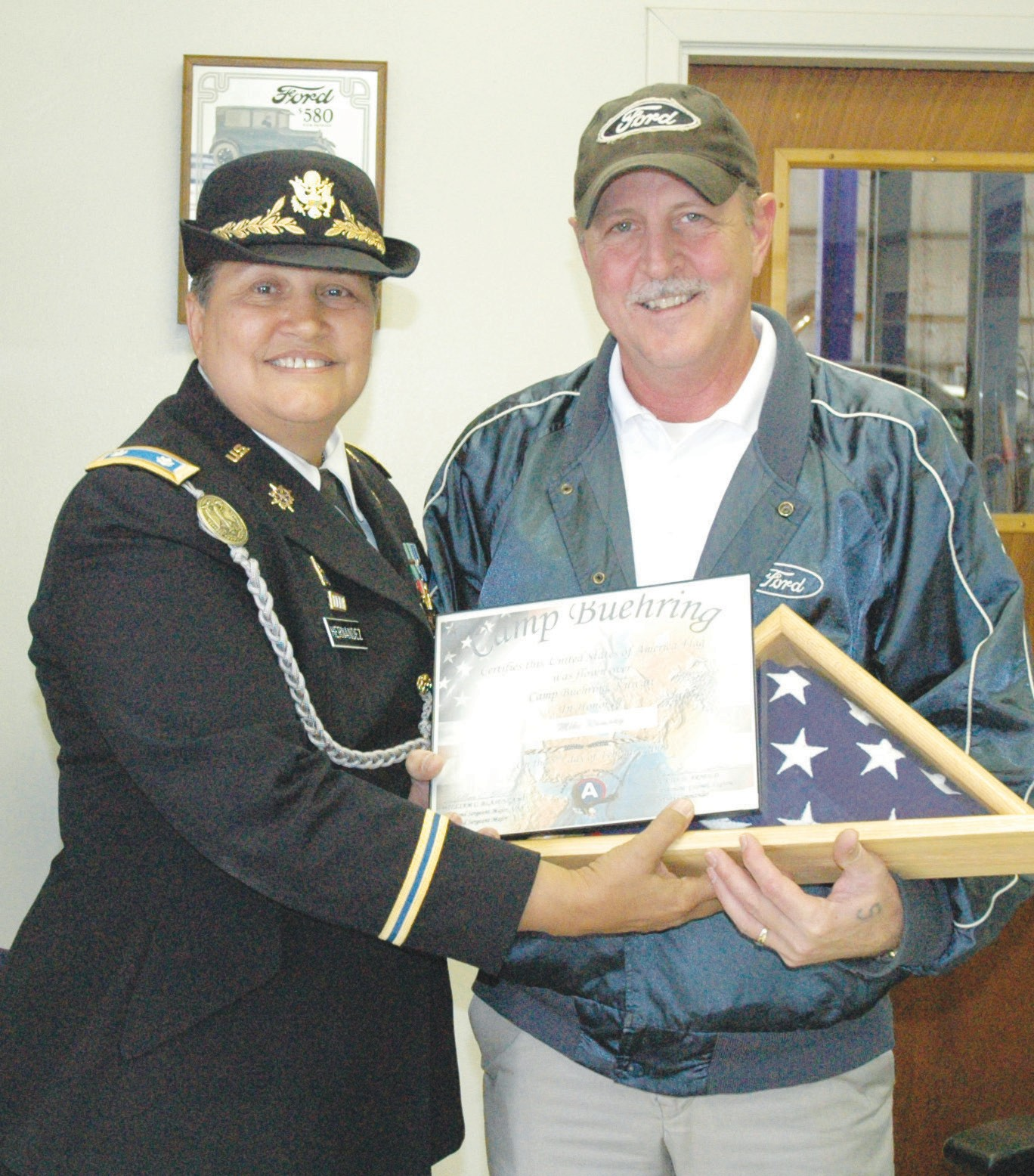 Mike Ramsey, service manager at Kinsel Ford in Pleasanton, receives a flag from LTC Retired U. S. Army Veronica R. Hernandez. It was flown over Camp Buehring, Kuwait during her 2009 tour.