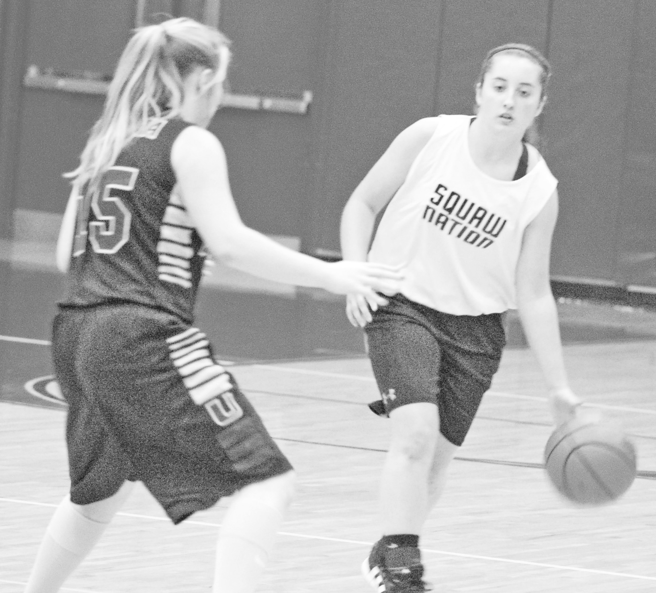Jourdanton's Laney Korus looks for open space while dribbling around a Utopia defender in a scrimmage last week. The Squaws open their regular season on the road against Odem Saturday at 2 p.m.