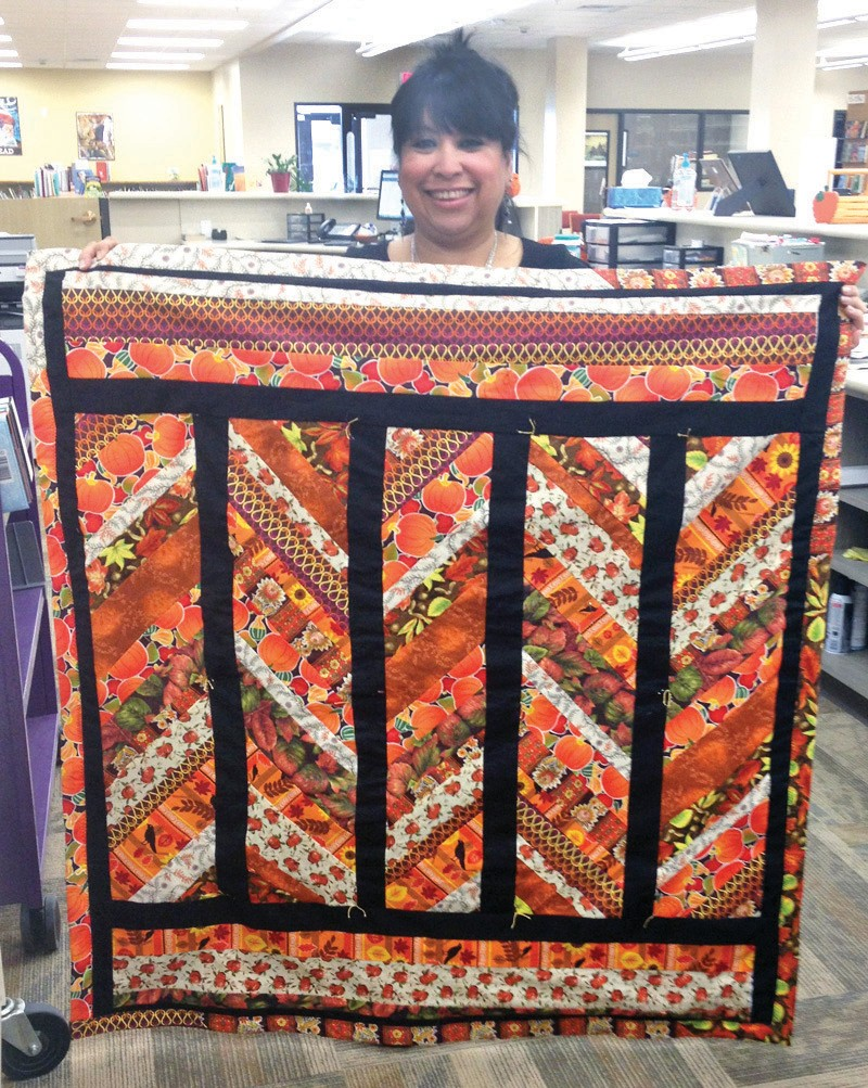 Danielle Rangel displays the beautiful hand-made Fall quilted throw/ wall hanging. Tickets are only $1 each or 6 for $5 and proceeds go to the Friends of the Pleasanton Library. The drawing will be held Tuesday, November 25, just in time for your Thanksgiving holidays. Wouldn't it look great on your festive table? Drop by the library to see the quilt and pick up a couple of tickets. Call 569-5901 for information.