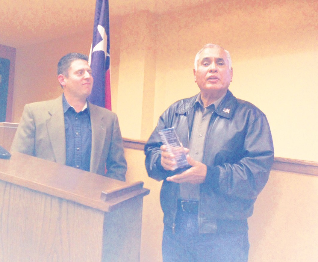Joe Rodriguez, outgoing representative for Atascosa County Appraisal District, receives a plaque of appreciation from Mayor Clint Powell, council and staff for his dedication in representing the City of Pleasanton.