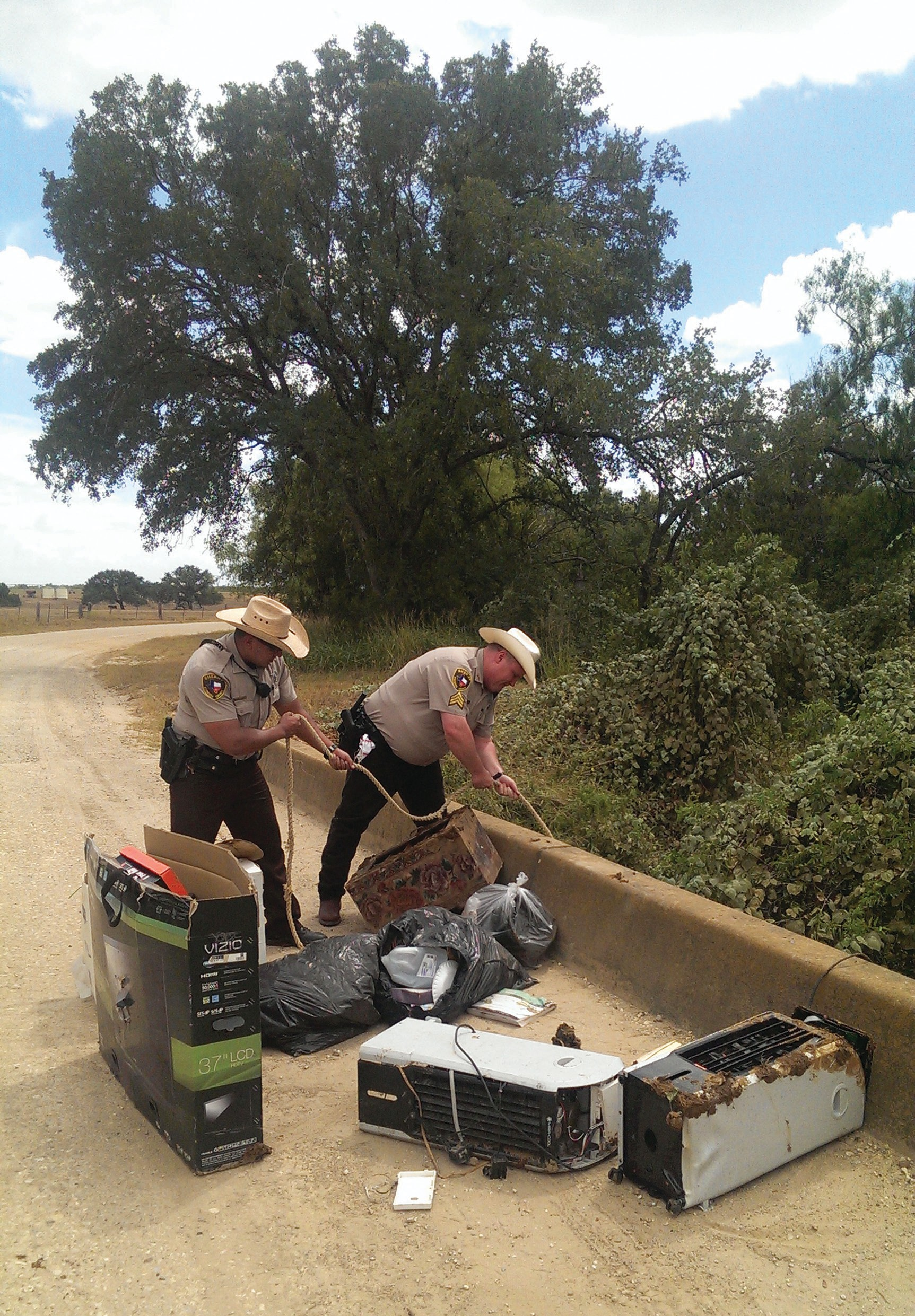Sergeant Deputy Kevin Draughn and Deputy Michael Castaneda are seen here hoisting up items dumped off of a bridge near Jourdanton recently. The person responsible for this dumping has been identified.