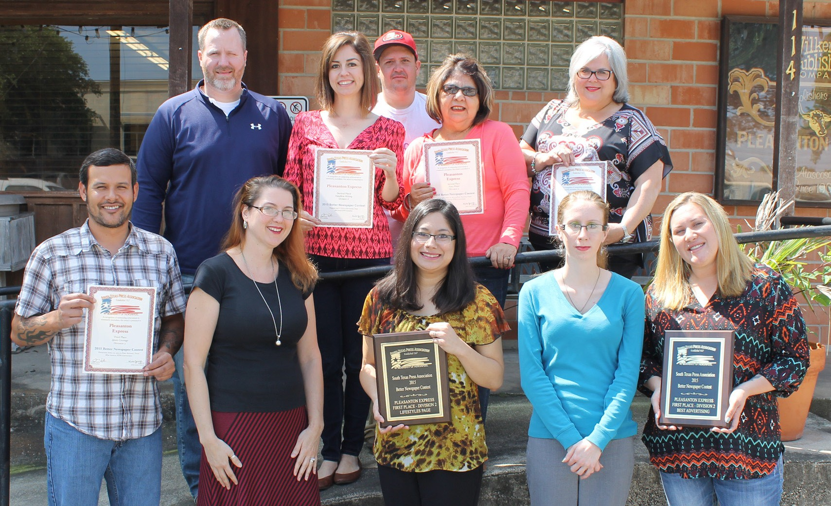 The Pleasanton Express staff brought home six awards from the South Texas Press Association Better Newspaper contest held last week. Left to right, front row are Sports Editor Chris Filoteo with the third place certificate for Sports Coverage, Business/Classified/Circulation Manager Rhonda Chancellor, Living Editor Lisa Luna with the plaque for first place in Lifestyle Pages, Katelyn Scott (Ads/Imaging) and Advertising Manager Megan Benishek with the first place plaque for Display Advertising. Second row are James Sharp (Advertising Representative), Ag and Obits Editor/Columnist Robbie Hamby with the second place Headline Writing certificate, Aaron Davidson (Ads/Imaging); Newsroom Manager Hope Garza with the second place News Photo and Editor Sue Brown holding the second place certificate for General Excellence. Missing from the photo is Leon Zabava, Oil and Gas Editor. The Express came in second overall in the Sweepstakes division, too.