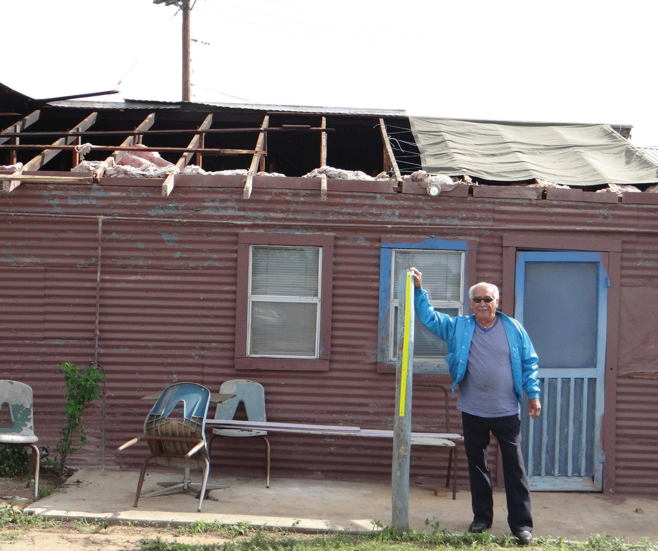 Smitty Gallegos of Gallegos' Place stands next to his damaged building from the storms that brewed over the weekend. Tornado-like winds ripped off his ceiling, loosened wires and twisted tree limbs on his property located south of Pleasanton on Hwy. 281.