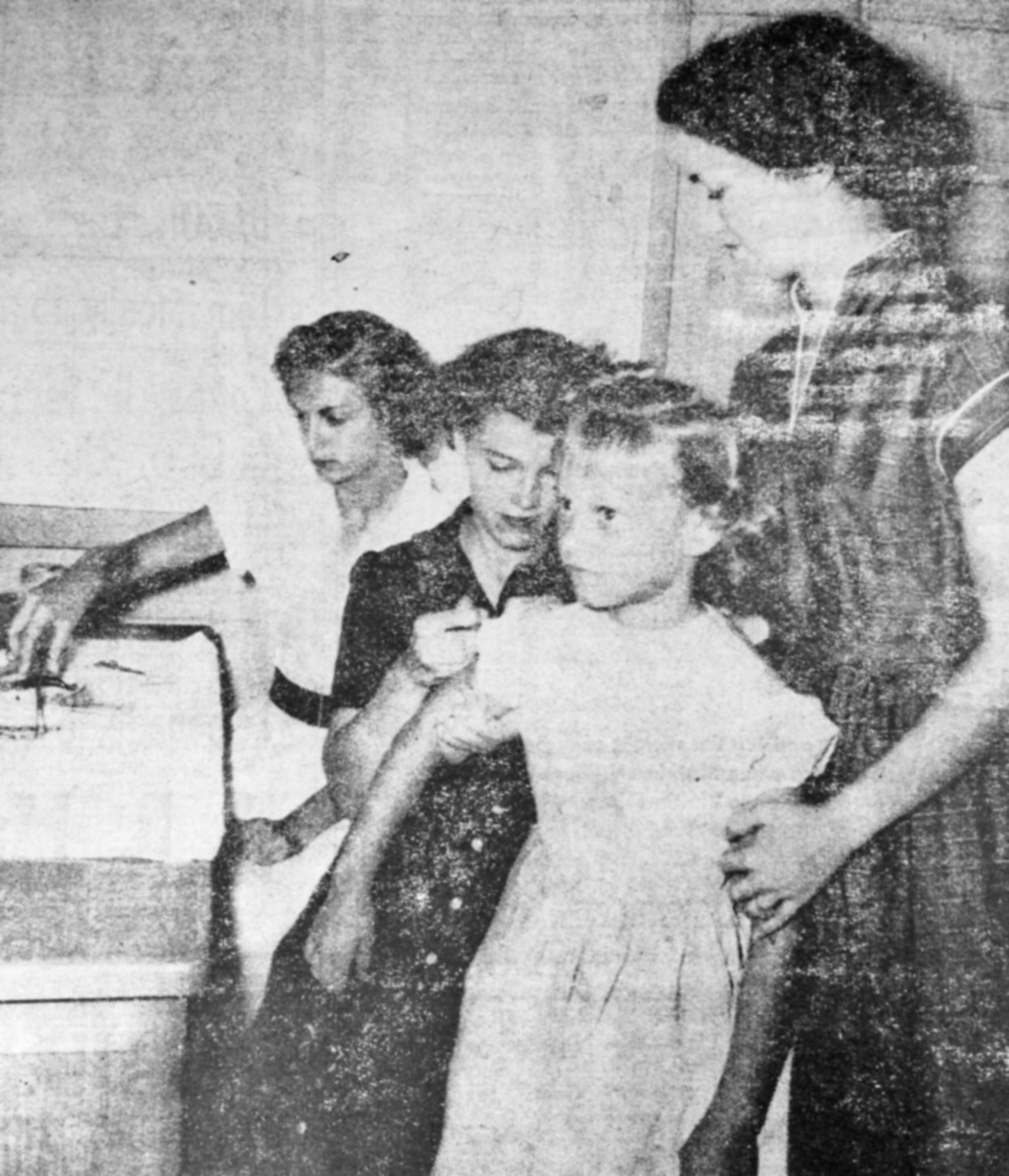 First polio shot-First youngster to get a polio shot at Poteet was Kathy Hayes, second grader. A brave little girl, Kathy looks a little dubious about the whole thing but she didn't complain. It was suspected that besides getting a polio shot, Kathy might also be getting the measles. She was the first in line because she wasn't feeling too well. Giving the shot is Mrs. Harriet Fischer, school nurse. Standing next to Kathy is Evon Harrison and Marie Dauwe is at the far left. Photo originally ran in the April 28, 1955 edition of the Pleasanton Express.