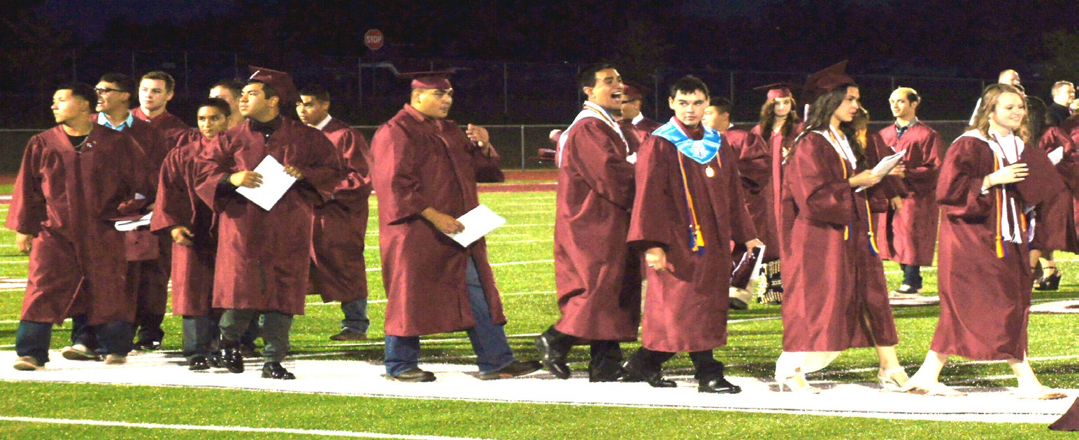 Newly graduated Poteet Seniors leave the football field after their commencement last Friday, May 29.