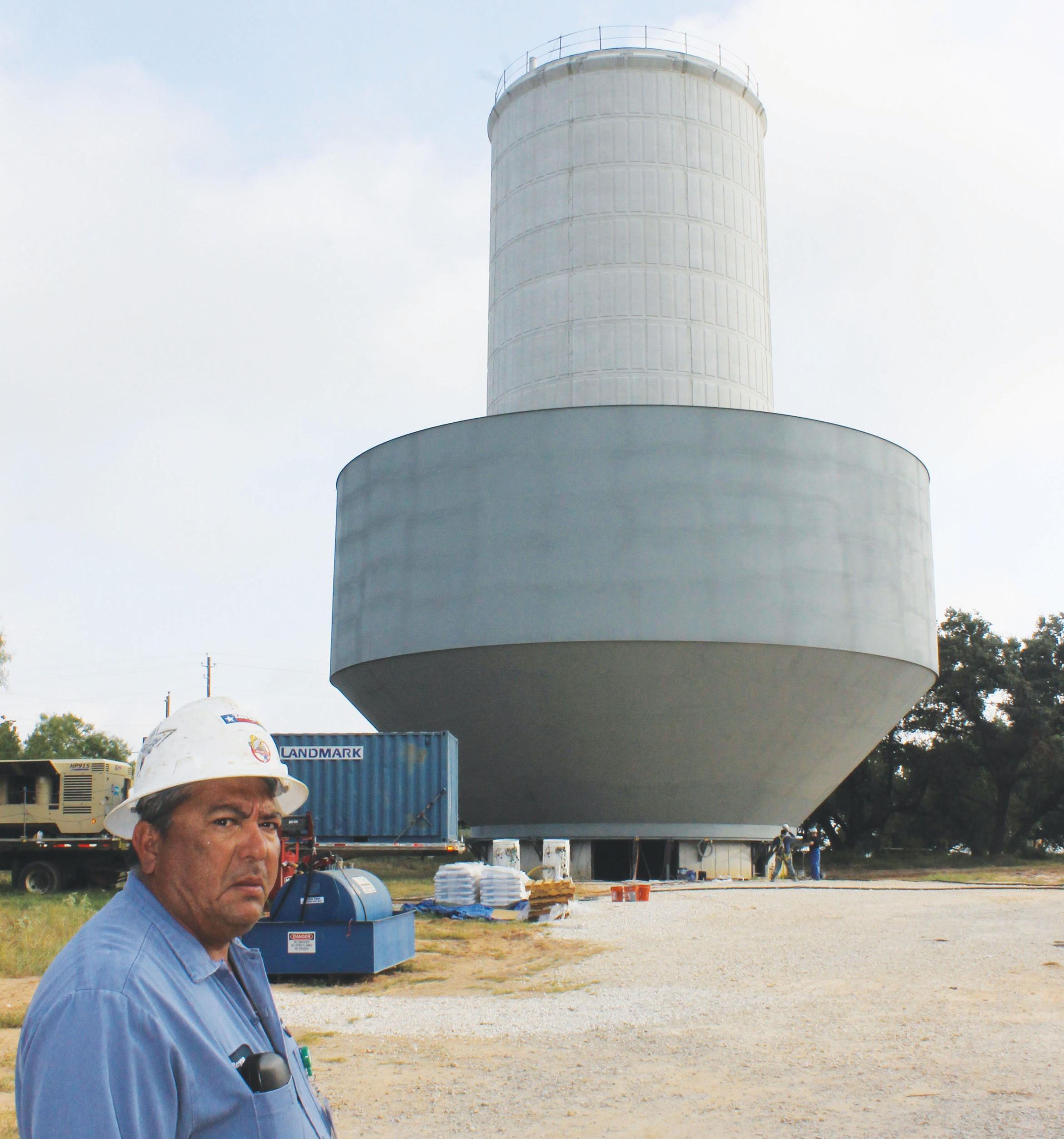 Doroteo Reyna, Pleasanton utility construction foreman, in the foreground of the construction site of the million and a quarter gallon water tower on Crestline. Notice two workmen being dwarfed at the lower right base of the water tank. Upon completion in late August, the tank will be hoisted to the top of the pedestal in small increments that will take from six to eight hours to complete.
