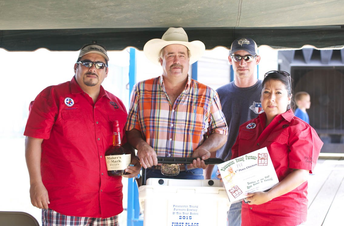 PYF 1ST PLACE CHICKEN The Pit Boss Smokers, Matias Serrata (left) and Maribel Cuellar (right) won first place with their chicken. PYF Chair Randy Rice and PYF President Dustin Neal present them with their plaque, cooler and Maker's Mark whisky.
