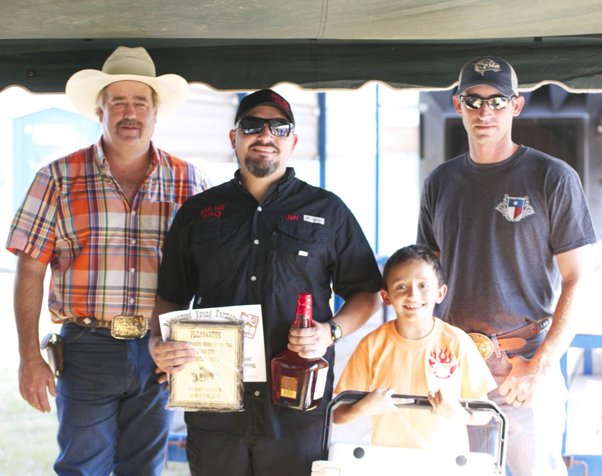PYF 1ST PLACE BRISKET Winning first place in the brisket category was Bad Ash BBQ's Jeff Kirchener and his son Jack. PYF Chair Randy Rice and PYF President Dustin Neal present him with their plaque, cooler and Maker's Mark whisky.