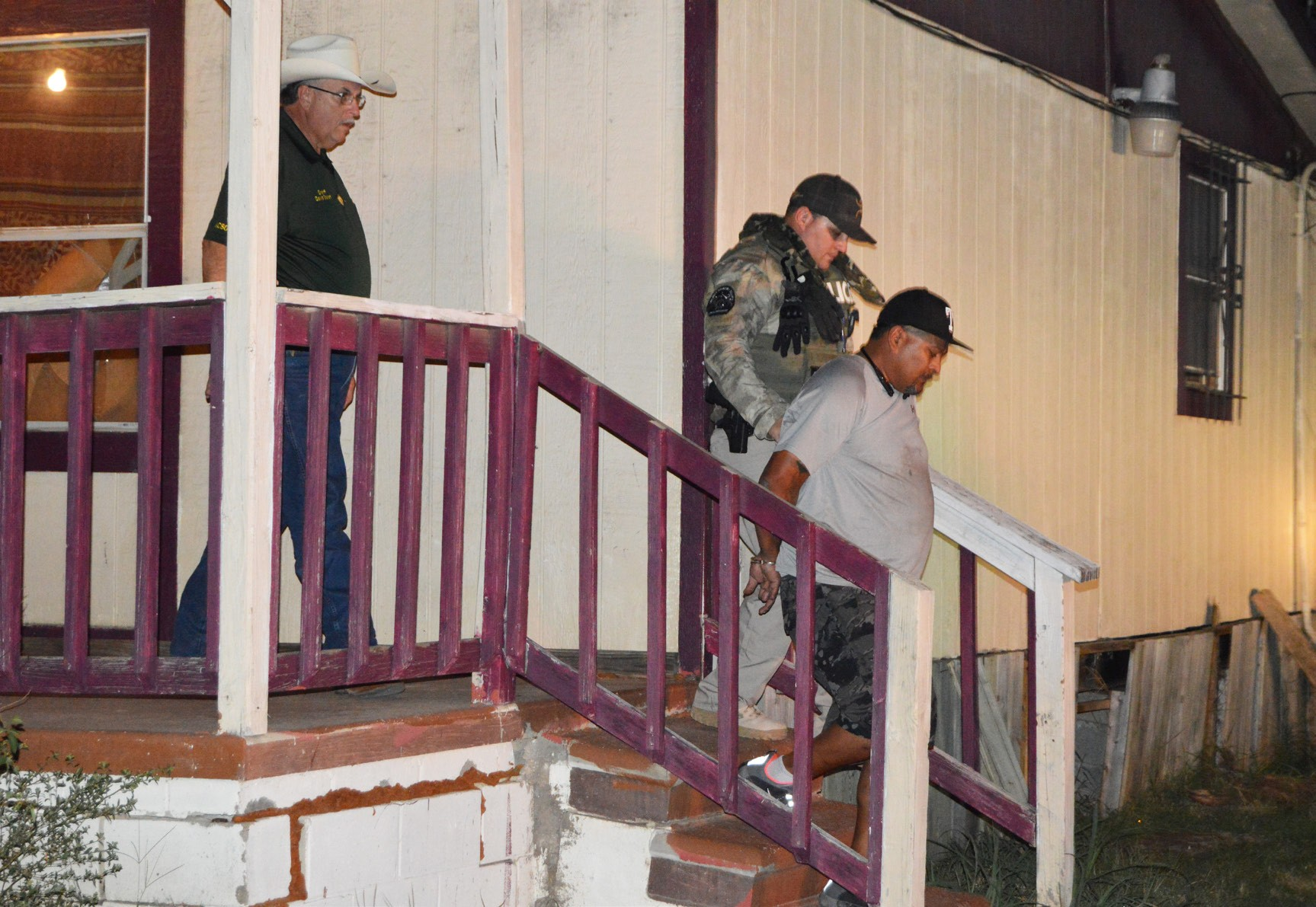Sheriff David Soward and Deputy J. D. Ruiz lead suspect Paul Belmon out of an illegal gaming house after a Saturday night raid on the business located at 10822 N. Hwy. 281.