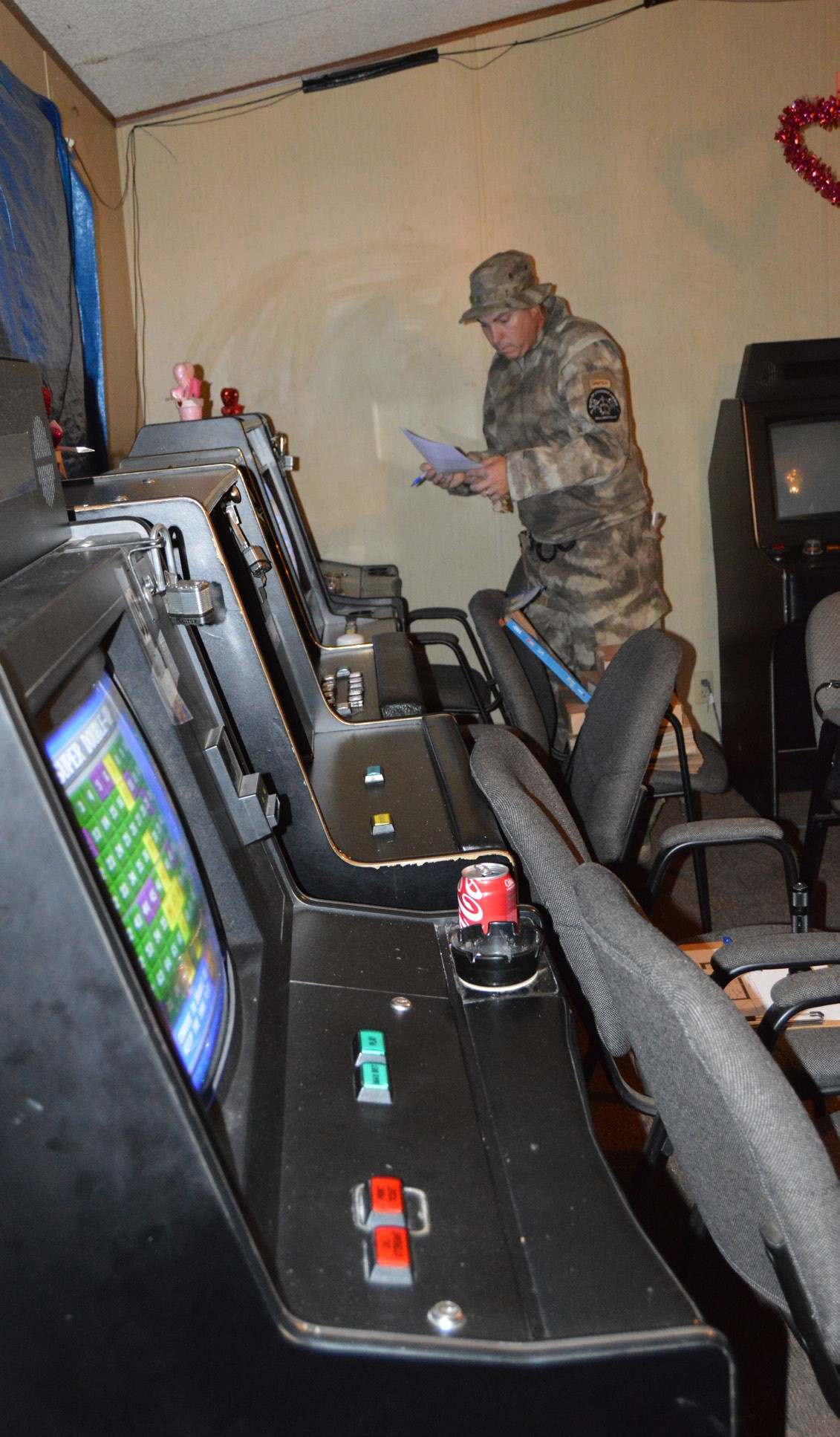 Sergeant Deputy Robert Newman surveys the illegal gambling machines before the motherboards are removed, rendering them useless.