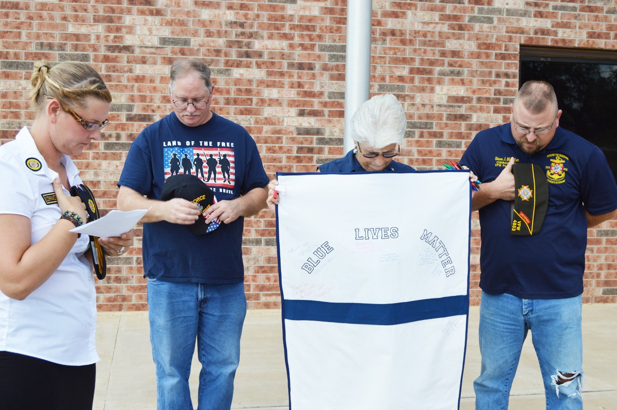 Flags flew at half-staff during the moment of silence as well as the entire day on Friday. Commander Theresea Cruz (left) offered a prayer as Jim Wilson (member and retired law enforcement), Debbie Wright and Steve J. Mueller Commander at the VFW.