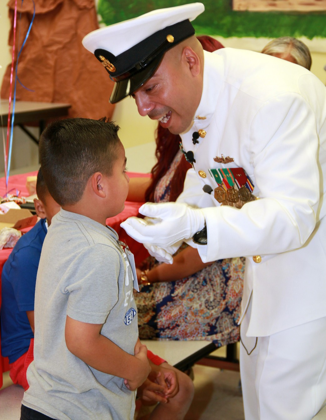 Brothers Vinny and Adyn Macias greet their father, Senior Chief Petty Officer Vincent Macias at his homecoming Tuesday during lunch.