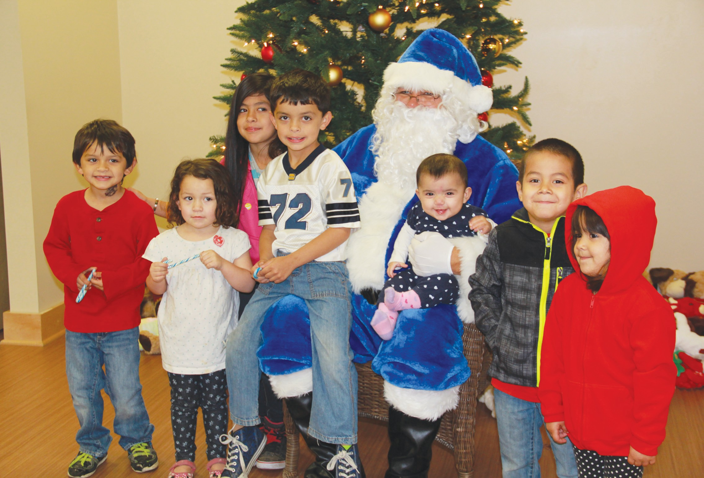 Erika Vela | PLEA SANTON Local children visited with Blue Santa and received stuffed animals and gifts donated by the community.