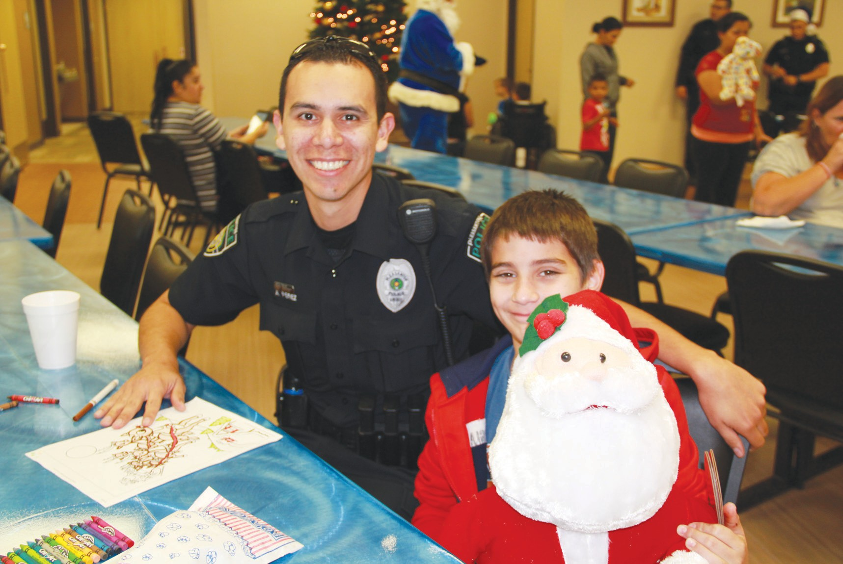 Officer Anastacio Perez interacted with Donovan Alaniz and other local children at the Blue Santa Party.