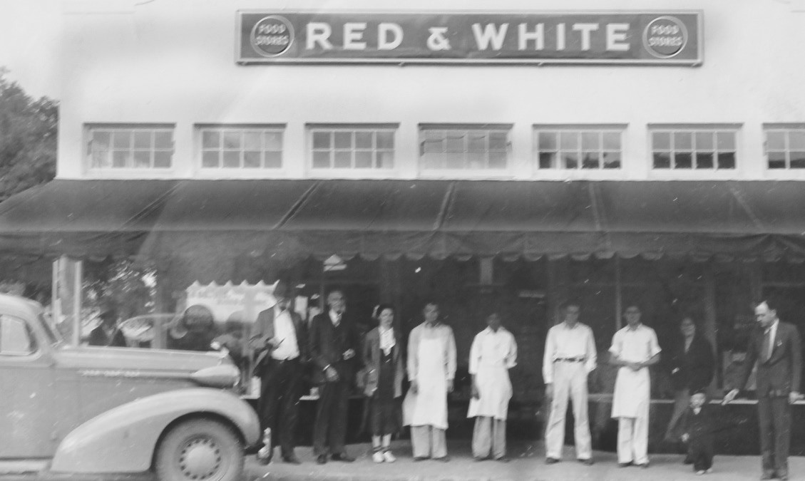 Photo of Ricks Red & White Store on Main St. in Pleasanton in 1937. At far right is Lee Ricks, Jr., about 2 years old with Lee Ricks, Sr. standing at the right. Others in the photo, from left, are Bob Lauderdale, F. B. Ricks, Maggie Wheeler, Charlie Vickers, Ben Rodriguez, Nook Brauchle, Margarito Rodriguez and Artie Jahn.