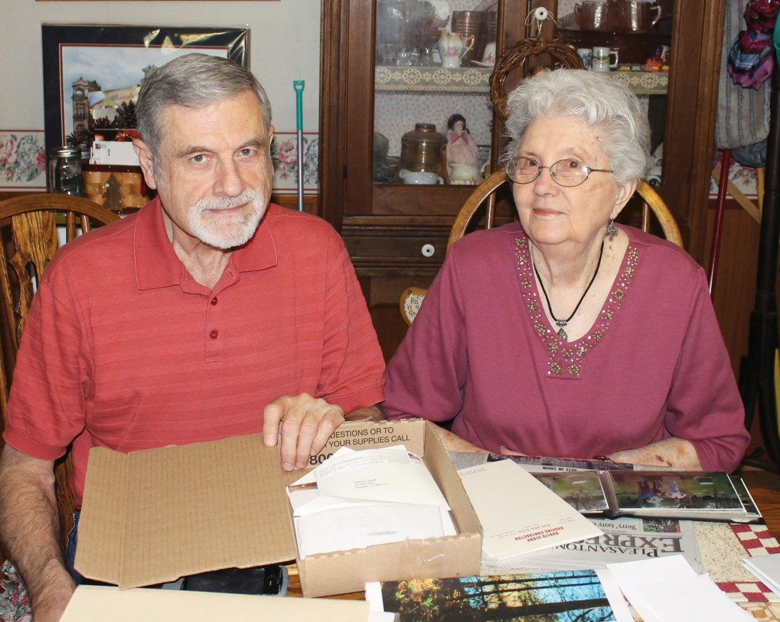 Martin Soward, III, with his mother, Mildred Soward, going through scrapbooks.