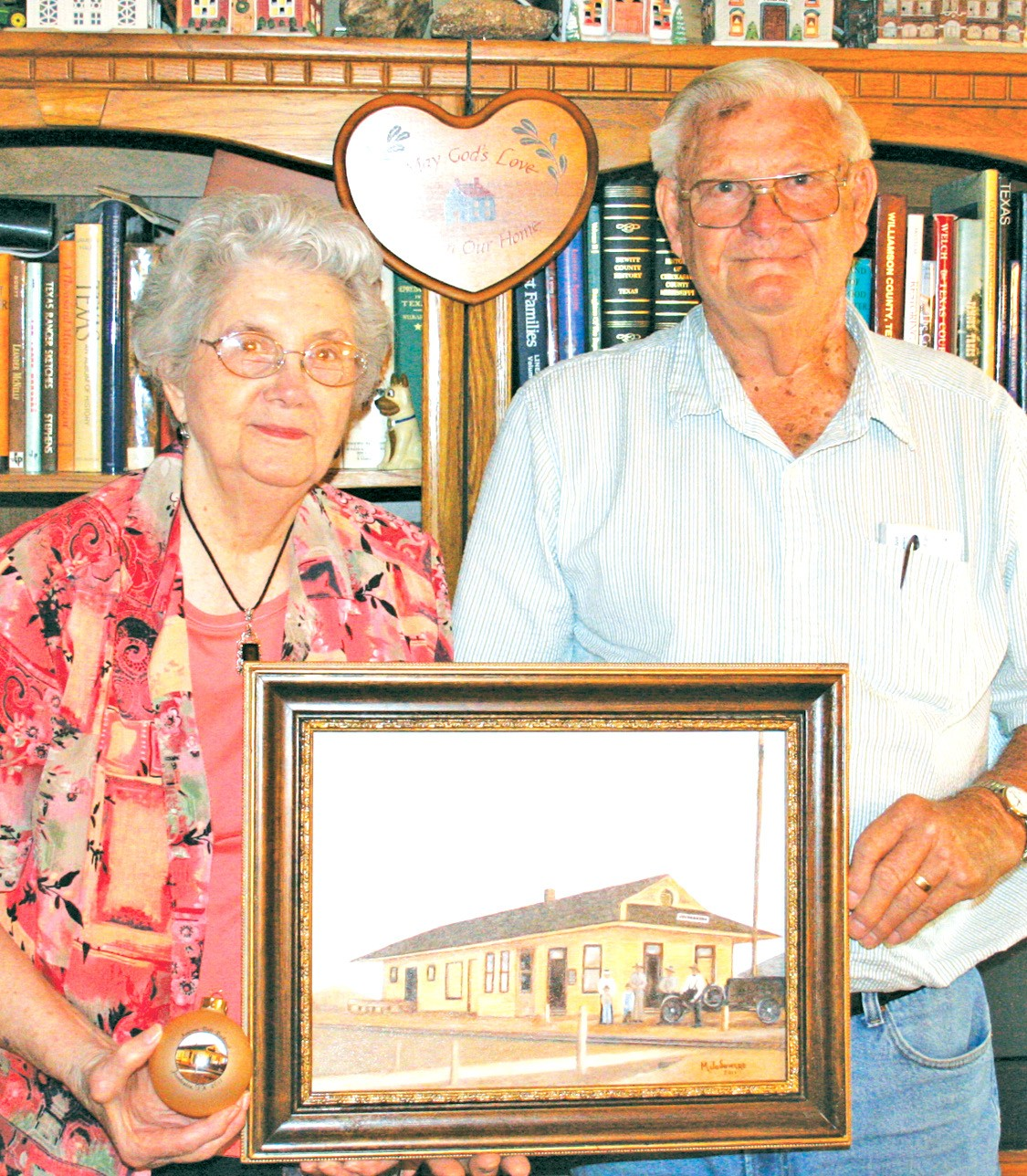Mildred and brother, Norman Porter, Sr., with her painting and glass Christmas ornament of the Artesian Belt depot in Jourdanton.