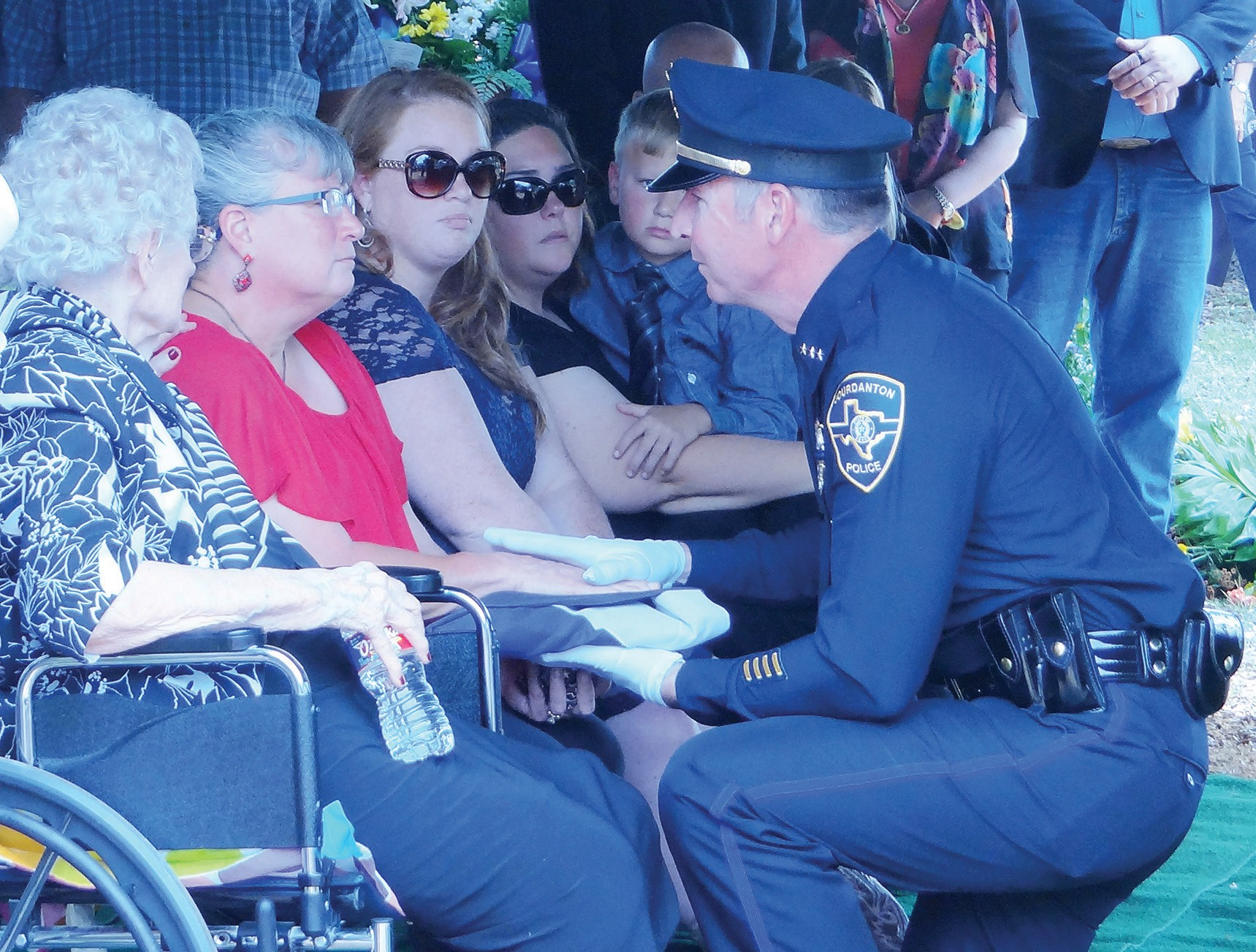 Jourdanton Police Department Chief Eric Kaiser presents the flag to Cathleen Rutherford, the widow of John Eric.