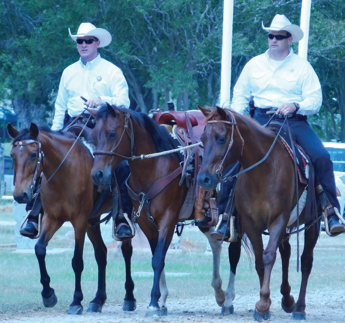 Texas Rangers Shane Staley and Terry Snyder lead John Eric's horse Dolly, in the procession. His boots are sitting reversed in the strirrups.