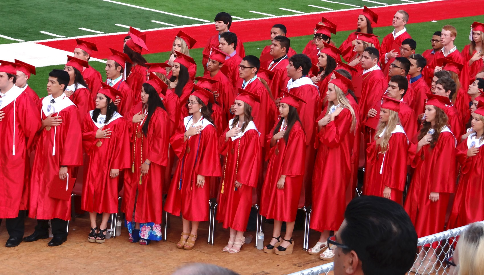 The Jourdanton High School Senior Class stands, hands over their hearts and says the Pledge of Allegiance during the commencement ceremony held Saturday, May 28 at Indian Stadium. As this chapter of their lives come to a close a new one begins all too soon. ROBBIE HAMBY | PLEASANTON EXPRESS