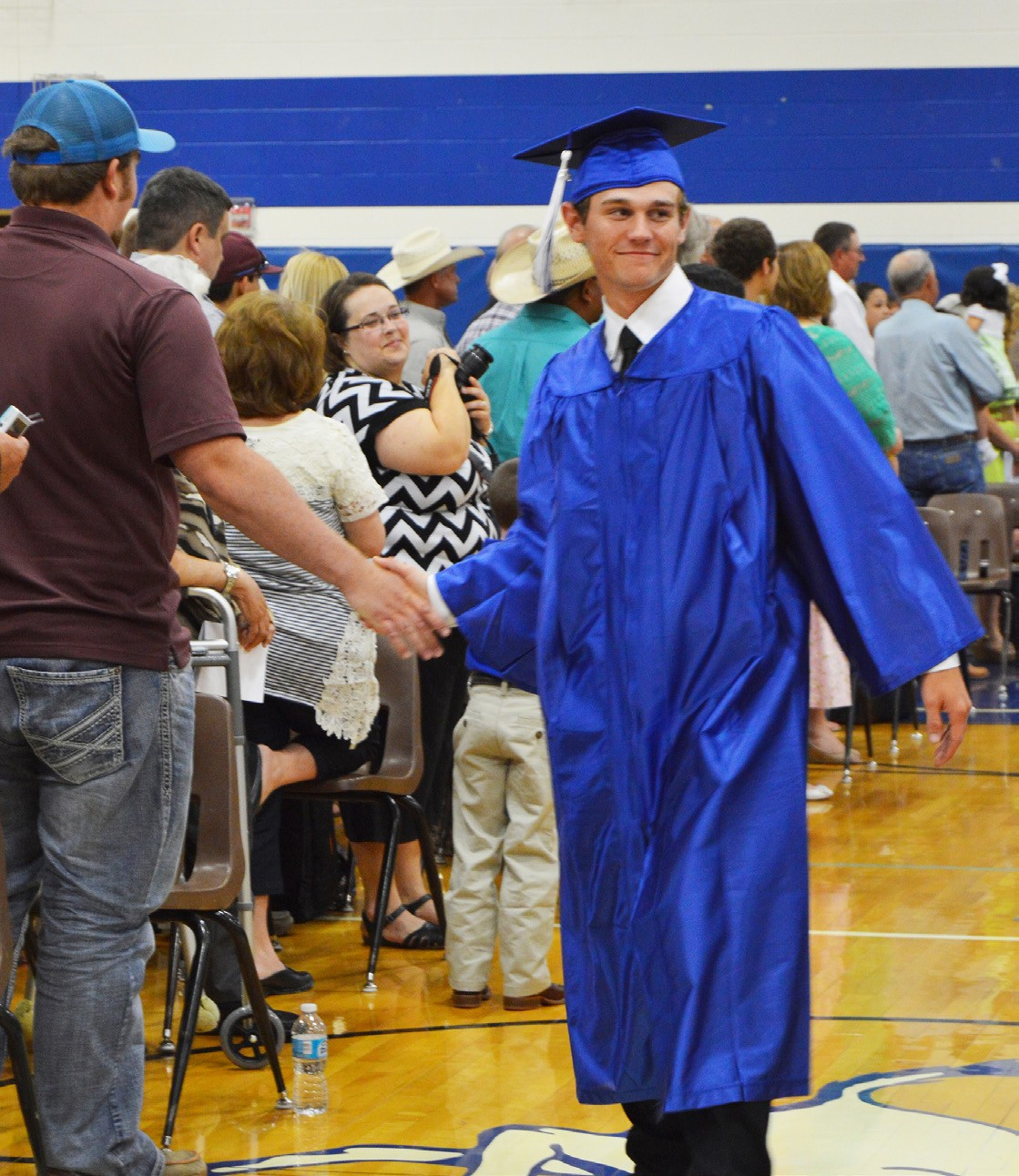 Tucker Smith, 2016 McMullen senior, gets a congratulatory hand slap from a friend in the audience during the commencement processional last Saturday evening.
